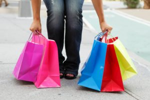 Close-up of a womans arms and legs as she picks up shopping bags from the ground.